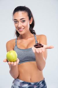 Smiling girl choosing between apple and chocolate