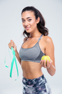 Happy fitness woman holding apple and measuring typ