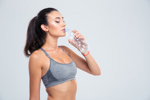 Beautiful sports woman drinking water