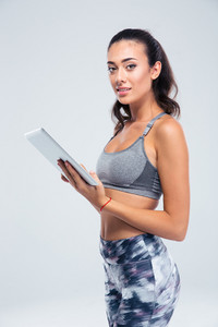 Happy sporty woman using tablet computer