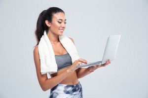 Fitness woman with towel using laptop