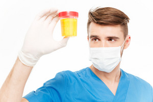 Male surgeon holding bottle of urine sample