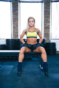Beautiful fit woman sitting on bench with dumbbells