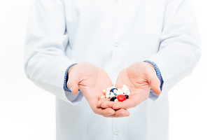 Male doctor holding pills