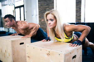 Woman and man doing push ups at gym