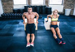 Man and woman workout with hands on fit box