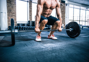 Muscular man workout with barbell