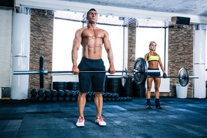 Muscular man and woman workout with barbell