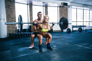 Woman workout with barbell and trainer