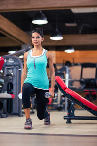 Woman workout with dumbbells in fitness gym