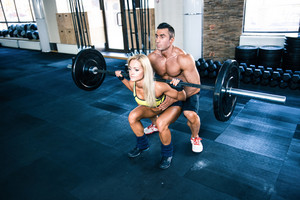 Woman workout with barbell with coach