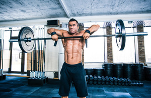 Handsome fitness man lifting barbell