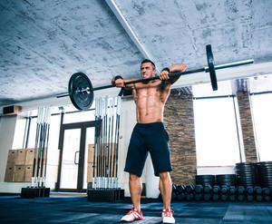 Muscular man lifting barbell