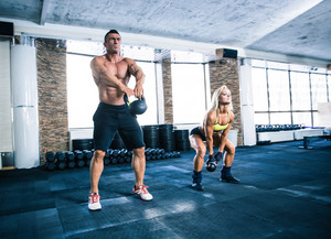 Group of a man and woman workout with kettle ball