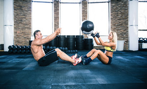 Group of a man and woman workout with fitball