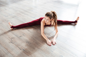 Attractive woman doing split on the floor