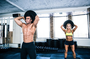 Muscular man and fit woman workout at gym