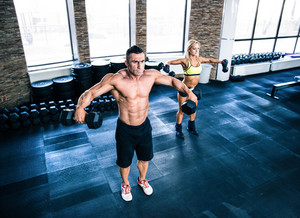Muscular man and fit woman workout with dumbbells