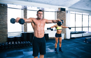 Muscular man and sporty woman lifting dumbbells