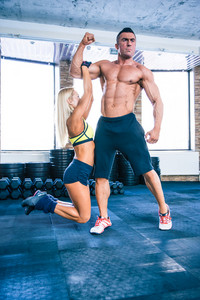 Fit woman hanging on a hand of muscular man