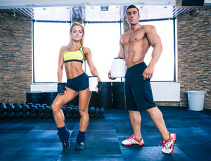 Muscular man and woman holding container with protein