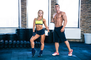 Man and woman holding container with protein at gym