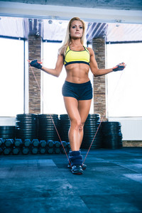 Young cute sporty woman workout with jumping rope