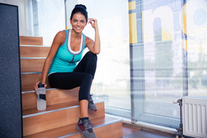 Woman resting on the stairs in gym