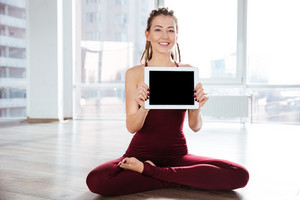 Happy woman sitting in yoga pose showing blank screen tablet