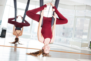 Cheerful attractive young sportswoman doing antigravity yoga exercise