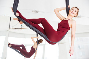 Happy woman relaxing on hammock in antigravity yoga studio
