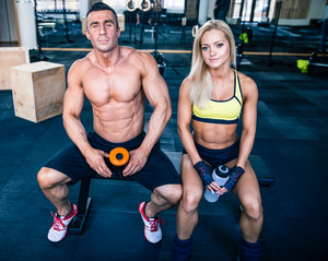 Man and woman sitting on the bench at gym