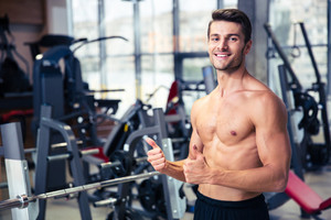 Muscular man showing thumbs up at gym