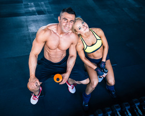 Muscular man and woman resting on bench at gym