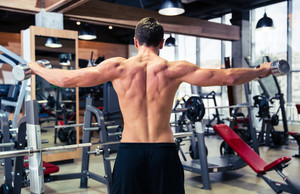 Back view portrait of man workout with dumbbells