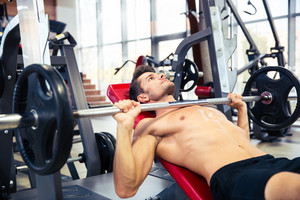 Man workout with barbell on the bench