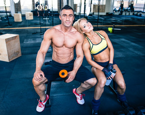 Handsome man and beautiful woman resting at gym