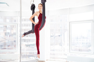 Pretty young woman doing antigravity yoga exercises in studio