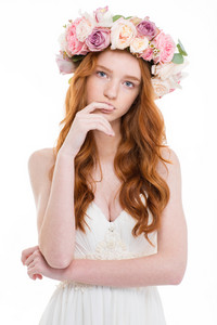 Beautiful redhead woman with wreath from flowers on head