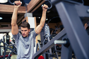 Fit man workout on fitness machine