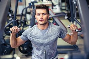 Bodybuilder workout on fitness machine at gym