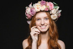 Smiling redhead woman with wreath from flowers on head