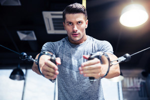 Man workout on fitness machine in gym