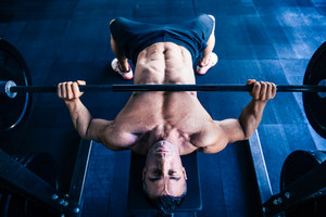 Muscular man workout with barbell on bench