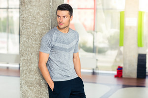Fitness man standing in gym and looking away
