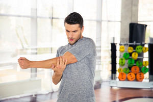 Man stretching hands at gym