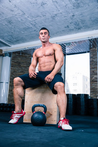 Muscular man sitting on fit box in gym