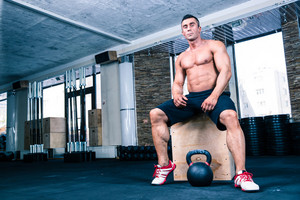 Muscular man resting in crossfit gym