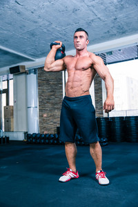 Bodybuilder workout with kettle ball in crossfit gym