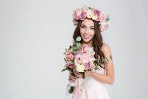 Charming smiling young bride in flower wreath with beautiful bouquet